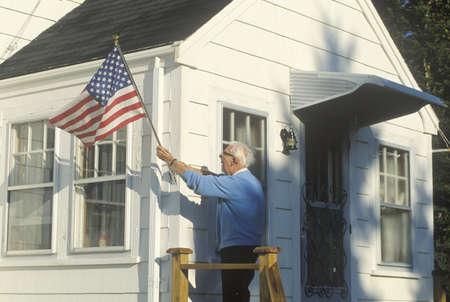Old Man Putting American Flag on House, Stonington, Maine