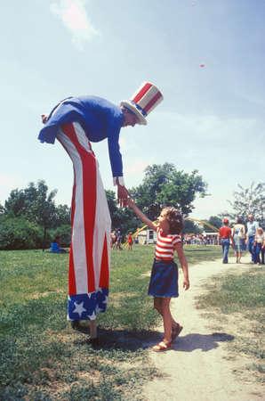 stilts: Uncle Sam on stilts Shaking Girls Hand, Salina, Kansas Editorial