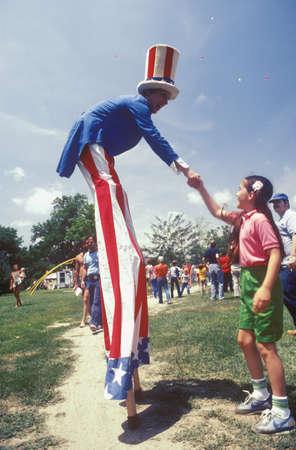stilts: Man on Stilts Dressed As Uncle Sam Shaking Girls Hand, Salina, Kansas Editorial