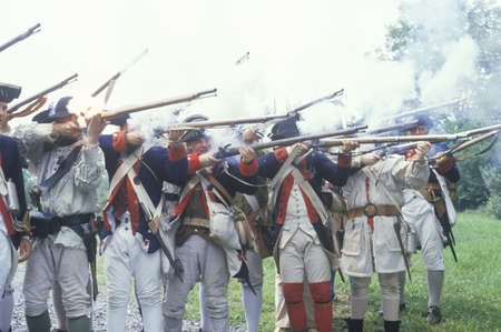 gunfire: Men dressed in 18th century American military infantry costume fire muskets during reenactment of American Revolutionary War