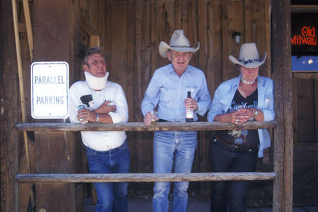 Group of cowboys in front of saloon in Lima, MT