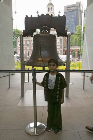center hall colonial: Child stands in front of Liberty Bell, at Liberty Bell Center, in front of Independence Hall in historic area of Philadelphia, Pennsylvania