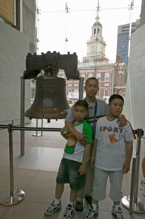 center hall colonial: Family stands in front of Liberty Bell, at Liberty Bell Center, in front of Independence Hall in historic area of Philadelphia, Pennsylvania