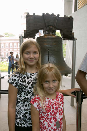 center hall colonial: Two blond sisters stand in front of Liberty Bell, at Liberty Bell Center, in front of Independence Hall in historic area of Philadelphia, Pennsylvania
