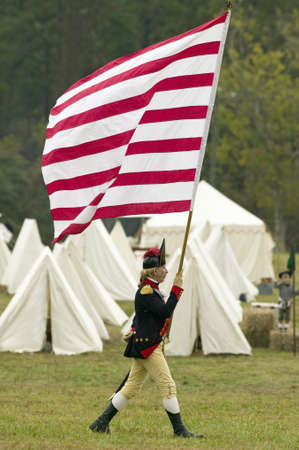 An early American flag is flown by solider on his way to Surrender Field at the 225th Anniversary of the Victory at Yorktown, a reenactment of the siege of Yorktown, where General George Washington commanded 17,600 American troops and French Comte de Roch