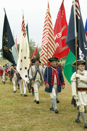tricorn hat: Patriot soldiers with flags march to Surrender Field as part of the 225th Anniversary of the Victory at Yorktown, a reenactment of the siege of Yorktown, where General George Washington commanded 17,600 American troops and French Comte de Rochambeau lead