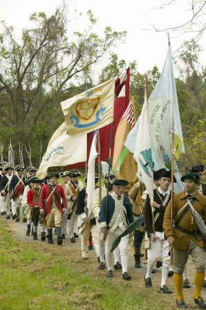 tricorne: Patriot soldiers with flags march to Surrender Field as part of the 225th Anniversary of the Victory at Yorktown, a reenactment of the siege of Yorktown, where General George Washington commanded 17,600 American troops and French Comte de Rochambeau lead