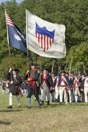 cir: Continentals on the march with early American Flags in re-enactment of Attack on Redoubts 9 & 10, where the major infantry action of the siege of Yorktown took place. General Washingtons armies captured two British fortifications, Endview Plantation (cir Editorial