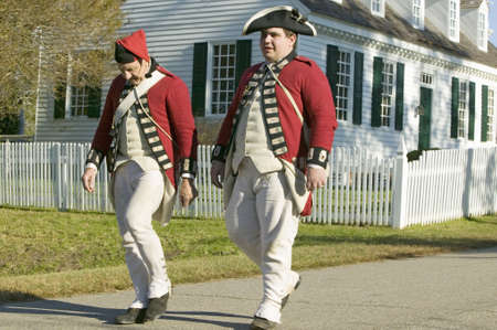 British soldiers walk in front of the Digges House, built in 1775 in Yorktown, Virginia. First owner Dudley Digges house now resides in the Colonial National Historical Park, Historical Triangle, Virginia.