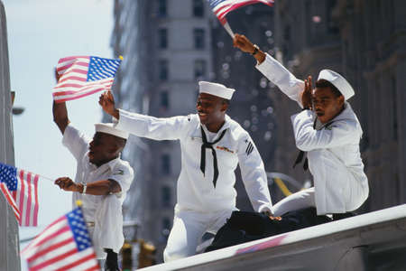 This is a Ticker Tape Parade showing the Desert Storm Victory Parade. It took place in the Canyon of Heroes where about 4.7 million people attended.  These are three sailors in white uniforms waving flags on a float. It demonstrates patriotism.