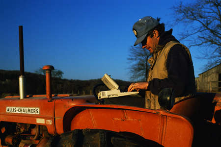 This is a close up of a farmer using a computer on his tractor.
