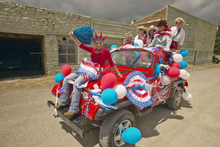 Teenagers riding a jeep decorated for the Fourth of July, in Lima Montana Stock Photo - 20713676
