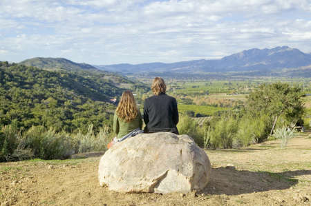Couple sits and meditates at Meditation Mounts Point overlooking the Ojai Valley, CA