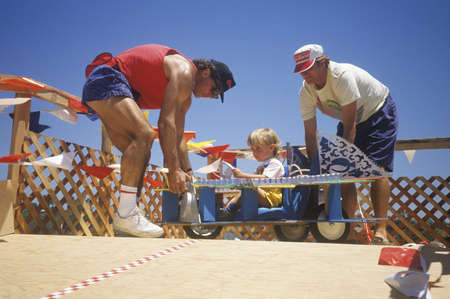 Two men assist a child about to race in the annual Soap Box Derby in Venice, California Редакционное