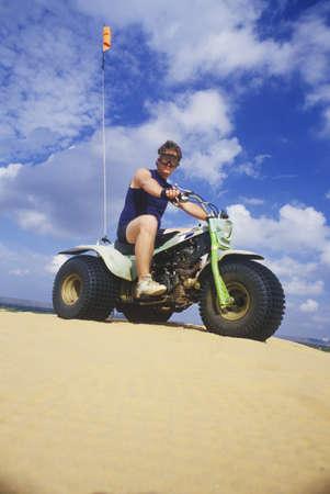 three wheeler: A man riding a three-wheeled all-terrain vehicle in Little Sahara State Park, Oklahoma