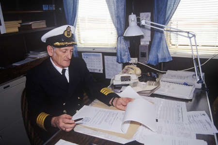 The captain of the ferry Bluenose doing paperwork at his desk, Maine Editorial