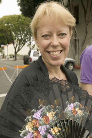 Blond woman with fan smiles at Old Spanish Days Fiesta held every August in Santa Barbara, California