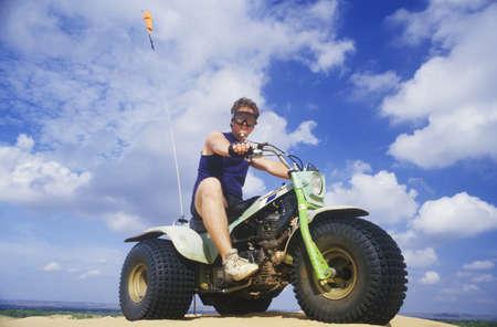 three wheeler: A man astride a 3-wheeled recreational vehicle in Little Sahara State Park, Oklahoma