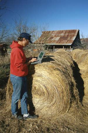 laptop: Farmer using laptop, leaning on hay bale