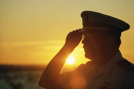 saluting: Military officer saluting at sunset Editorial