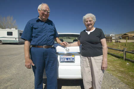 Elderly couple pose with California license plate that reads ÒPop loves MomÓ
