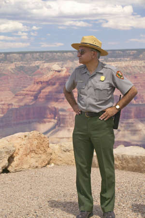 public park: Female National Park ranger looking at South Rim of Grand Canyon National Park in mid-summer in Arizona