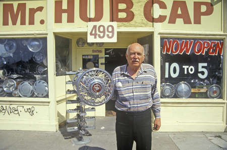shop sign: Man stands with hub cap in front of ÒMr. Hub CapÓ shop, San Jose, California