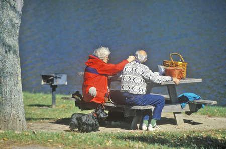 Seniors and Scottie dog picnic in autumn at Lake Waramug State Park, Connecticut