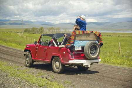 roughing: Bird watchers and red jeep in spring grasslands and mountains in Centennial Valley, Lakeview MT