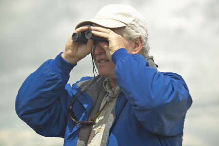 bird watcher: Bird watcher with binoculars in spring grasslands and mountains, Centennial Valley, near Lakeview, MT Editorial