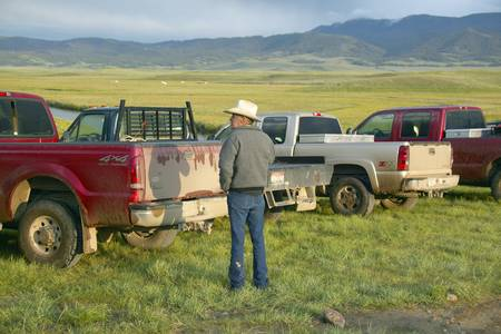 lakeview: Rancher and cowboy looking at pickup trucks in Centennial Valley, near Lakeview, MT Editorial
