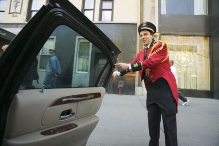 bellman: Bellman in red jacket opens limo door in front of Helmsley Park Lane Hotel on Central Park West, in Manhattan, New York City, NY