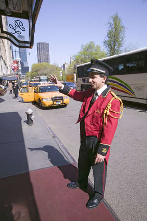 bellman: Bellman in red jacket calls for cab in front of Helmsley Park Lane Hotel on Central Park West, in Manhattan, New York City, New York
