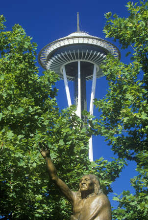 Space Needle with statue of Chief Seattle at base in Seattle, WA against blue sky