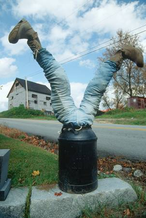 humor: Front yard art of legs protruding from milk can, New England Editorial