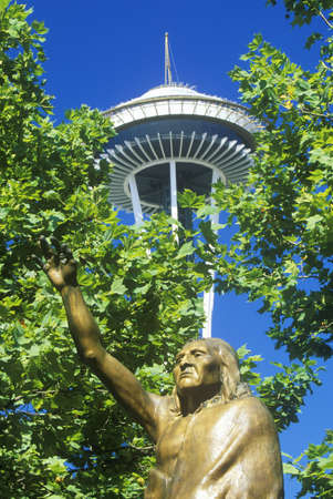 when: Space Needle with statue of Chief Seattle at base in Seattle, WA against blue sky