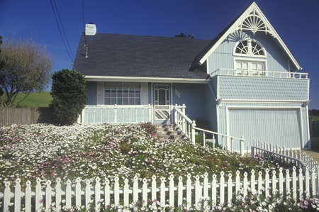 cape cod style: House with white picket fence in spring, CA