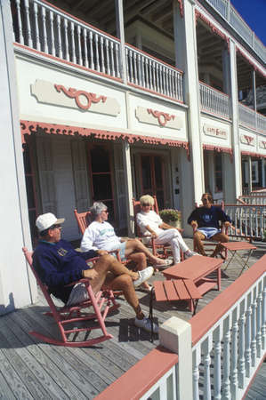 Tourists relaxing on a porch of a Victorian home, Cape May, NJ