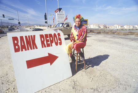 repo: Clown salesperson with Bank Repo sign at roadside dealership
