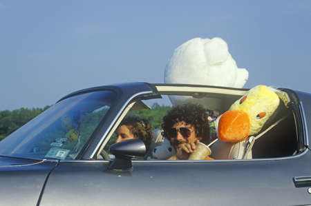 top down car: Driver with aviator sunglasses and stuffed animals in TransAm on New Jersey Turnpike