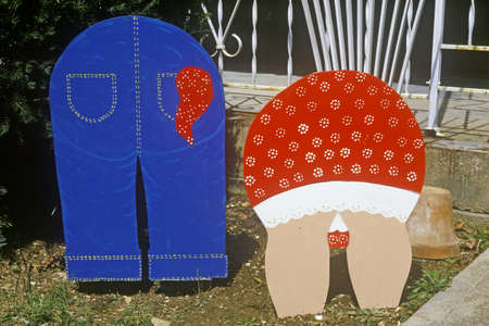 Cutout lawn ornaments of rear ends of couple gardening