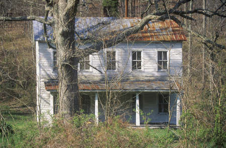 va: Deserted two-story clapboard home behind trees on Route 29, VA Editorial