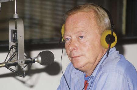 Radio disc jockey for station KFI in his studio, Los Angeles, CA