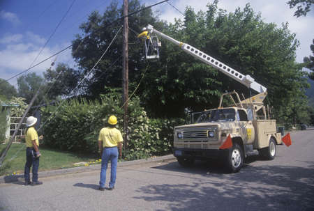 Cable television repairmen using a cherry-picker, Ojai, CA
