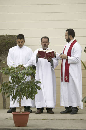 Three priests reading from the bible on Good Friday, Easter, at the beginning of the Passion play, a dramatic reenactment of the trial, torture and death of Jesus Christ at Christ the King Church and Our Lady of Guadalupe Parish, Oxnard, California, April