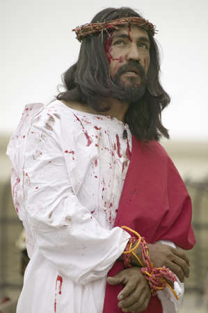 Close-up of an actor portraying Jesus Christ with blood on his face on Good Friday, Easter, during the Passion play, a dramatic reenactment of the trial, torture and death of Jesus Christ at Christ the King Church and Our Lady of Guadalupe Parish, Oxnard, Editorial