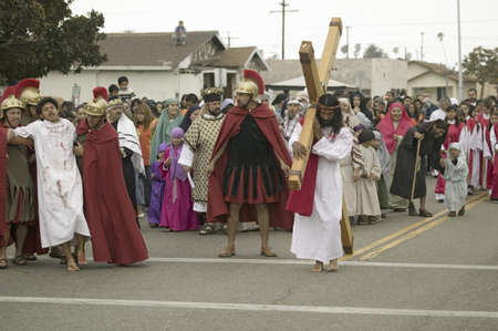 passion play: Roman soldiers overseeing reenactment of Jesus Christ carrying a cross past crowds on Good Friday, Easter, during the Passion play, a dramatic portrayal of the trial, torture and death of Jesus Christ at Christ the King Church and Our Lady of Guadalupe Pa