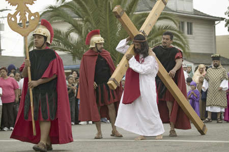An actor portraying Jesus Christ carrying a cross past crowds on Good Friday, Easter, during the Passion play, a dramatic reenactment of the trial, torture and death of Jesus Christ at Christ the King Church and Our Lady of Guadalupe Parish, Oxnard, Calif Editöryel