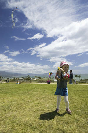 april 15: A young girl flying a kite in a deep blue sky on April 15, 2007, at the Santa Barbara Kite Festival, Santa Barbara City College, overlooking Pacific Ocean.