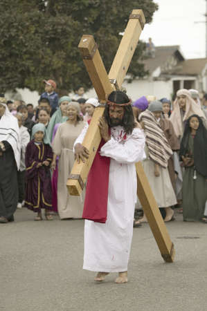 passion play: An actor portraying Jesus Christ carrying a cross past crowds on Good Friday, Easter, during the Passion play, a dramatic reenactment of the trial, torture and death of Jesus Christ at Christ the King Church and Our Lady of Guadalupe Parish, Oxnard, Calif Editorial